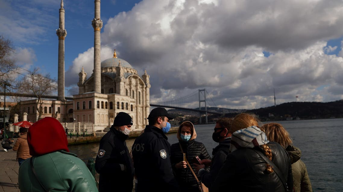 Turkish police officers check the passports of a group of Russian tourists at Ortakoy square during a nation-wide weekend curfew which was imposed to prevent the spread of the coronavirus disease (COVID-19) in Istanbul, Turkey February 28, 2021. (Reuters)