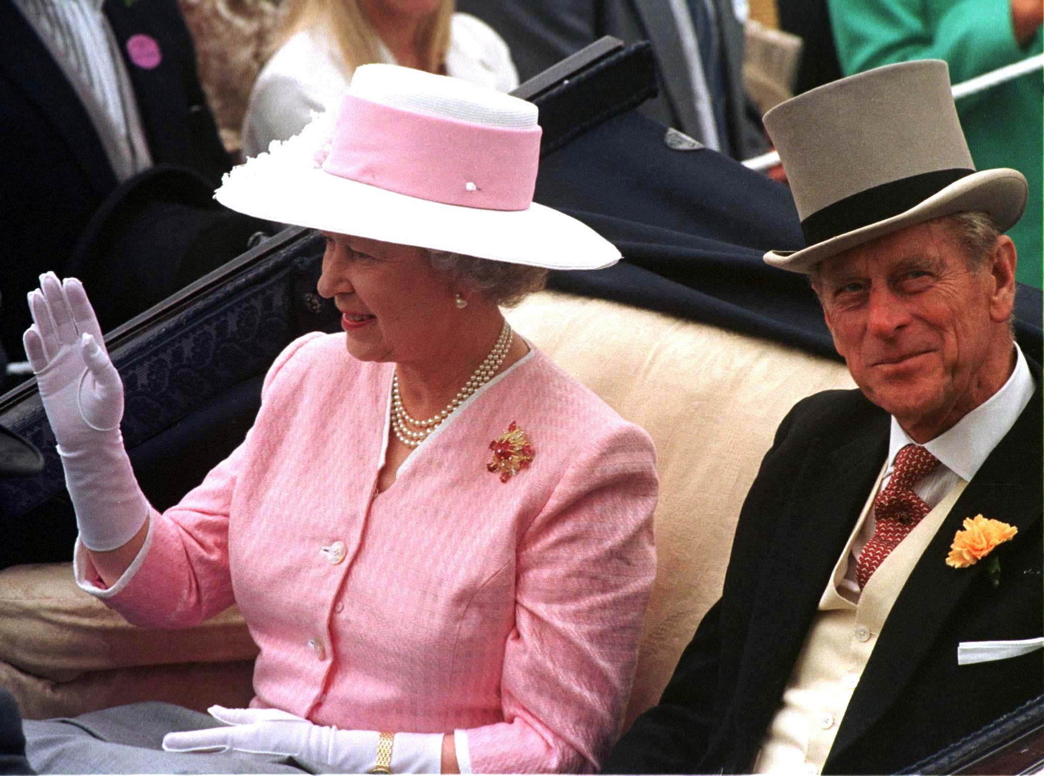 Queen Elizabeth II waves and Prince Philip smiles as their carriage is driven through the royal enclosure at the Royal Ascot racetrack June 17, 1997. Hundreds attended the first day of the annual event to see the fashions, royalty and the racing. BRITAIN