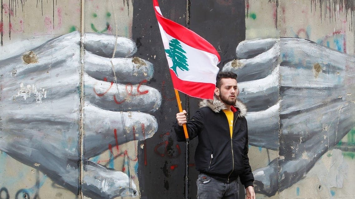 A man holds a Lebanese flag as demonstrators gather during a protest over the deteriorating economic situation, in Beirut, April 10, 2021. (Reuters)