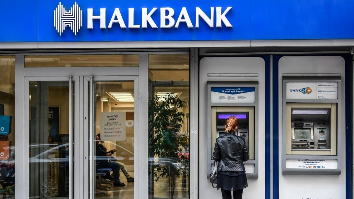 A woman uses an ATM machine at a branch of Turkish bank Halkbank on December 1, 2017 in Istanbul. (AFP)