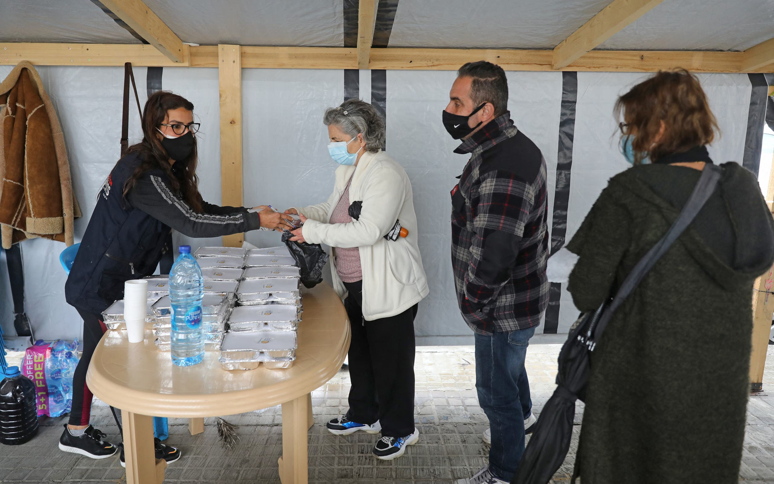 A volunteer gives out food handouts to people in need at the Lebanese Grassroots organisation in Beirut's Mar Mikhael district, which was hard hit by last year's port explosion, on March 24, 2021. (File photo: AFP)