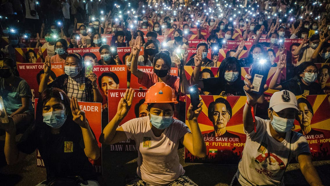 In this file photo taken on March 12, 2021, protesters hold up the three-finger salute and placards with the image of detained civilian leader Aung San Suu Kyi while using their mobile torches during a demonstration against the military coup in Yangon. Myanmar's ousted civilian leader Aung San Suu Kyi was hit with a fresh criminal charge on April 12, 2021, as the junta's tough crackdown on dissent rolls on. (File photo: AFP)