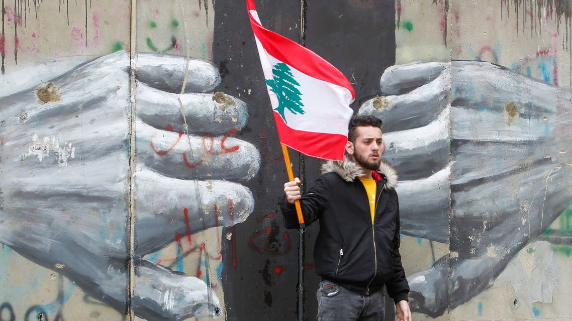 A man holds a Lebanese flag as demonstrators gather during a protest over the deteriorating economic situation, in Beirut, Lebanon April 10, 2021. (File photo: Reuters)
