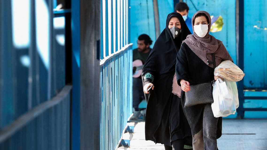 People wearing protective masks amid the coronavirus pandemic walk on a street in Iran's capital Tehran, on April 5, 2021. Iran's daily new COVID-19 infections reached a four-month high, said the health ministry, as the capital Tehran was put on the highest virus risk level.