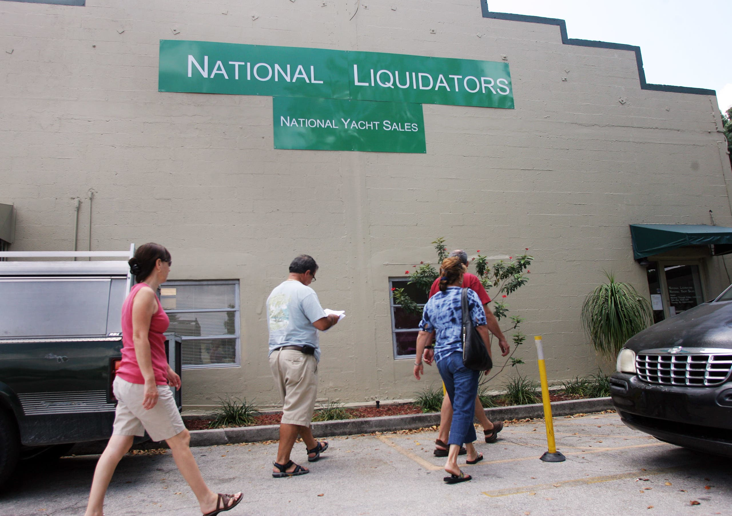 People walk outside of National Liquidators in Ft. Lauderdale, Fla., on Wednesday April 1, 2009, where financier Bernie Madoff's 55-foot yacht named Bull is being held after being seized by federal authorities. (AP)