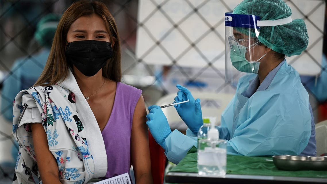 A medical personnel administers the CoronaVac vaccine, developed by China's Sinovac firm, to a woman, during a vaccination campaign to contain the spread of Covid-19 coronavirus cluster traced to entertainment venues, at Saeng Thip sports ground in Bangkok on April 8, 2021.