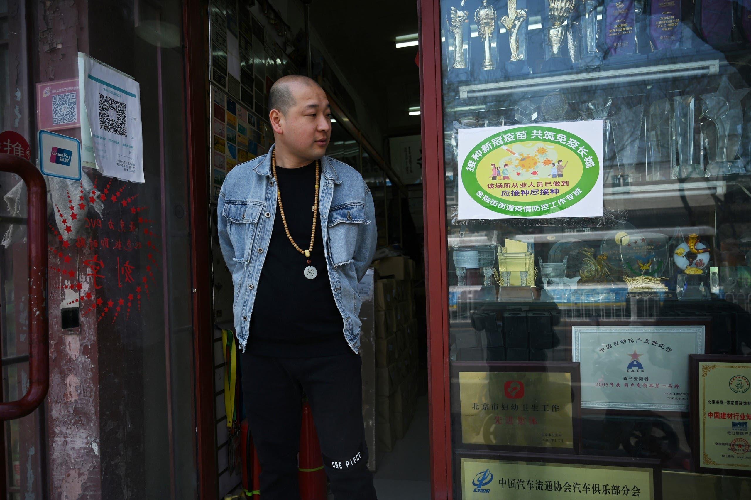 علامة خضراء على باب متجر في بكين تشير إلى أن معظم العاملين فيه تلقوا اللقاح
