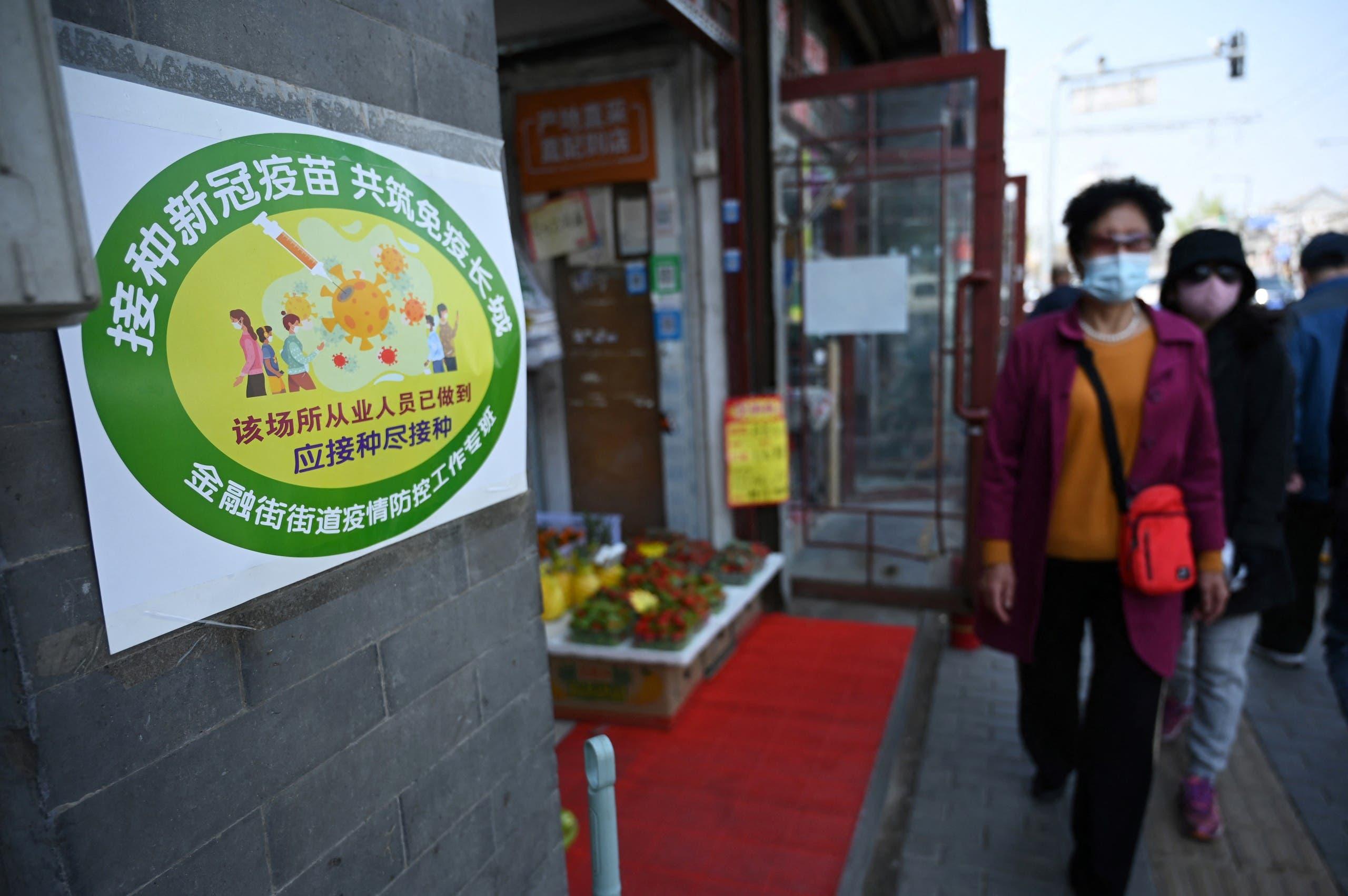 علامة خضراء على باب متجر خضار في بكين تشير إلى أن معظم العاملين فيه تلقوا اللقاح