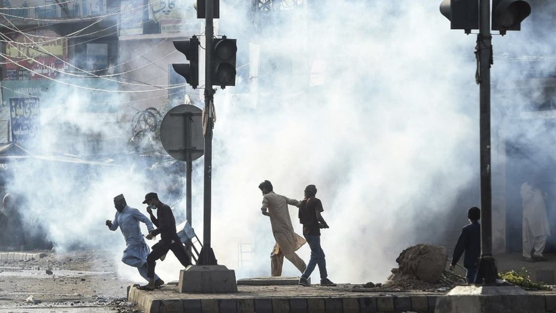 Supporters of Tehreek-e-Labbaik Pakistan (TLP) party disperse after police fired tear gas during a protest against the arrest of their leader as he was demanding the expulsion of the French ambassador over depictions of Prophet Muhammad, in Lahore on April 13, 2021. (AFP)