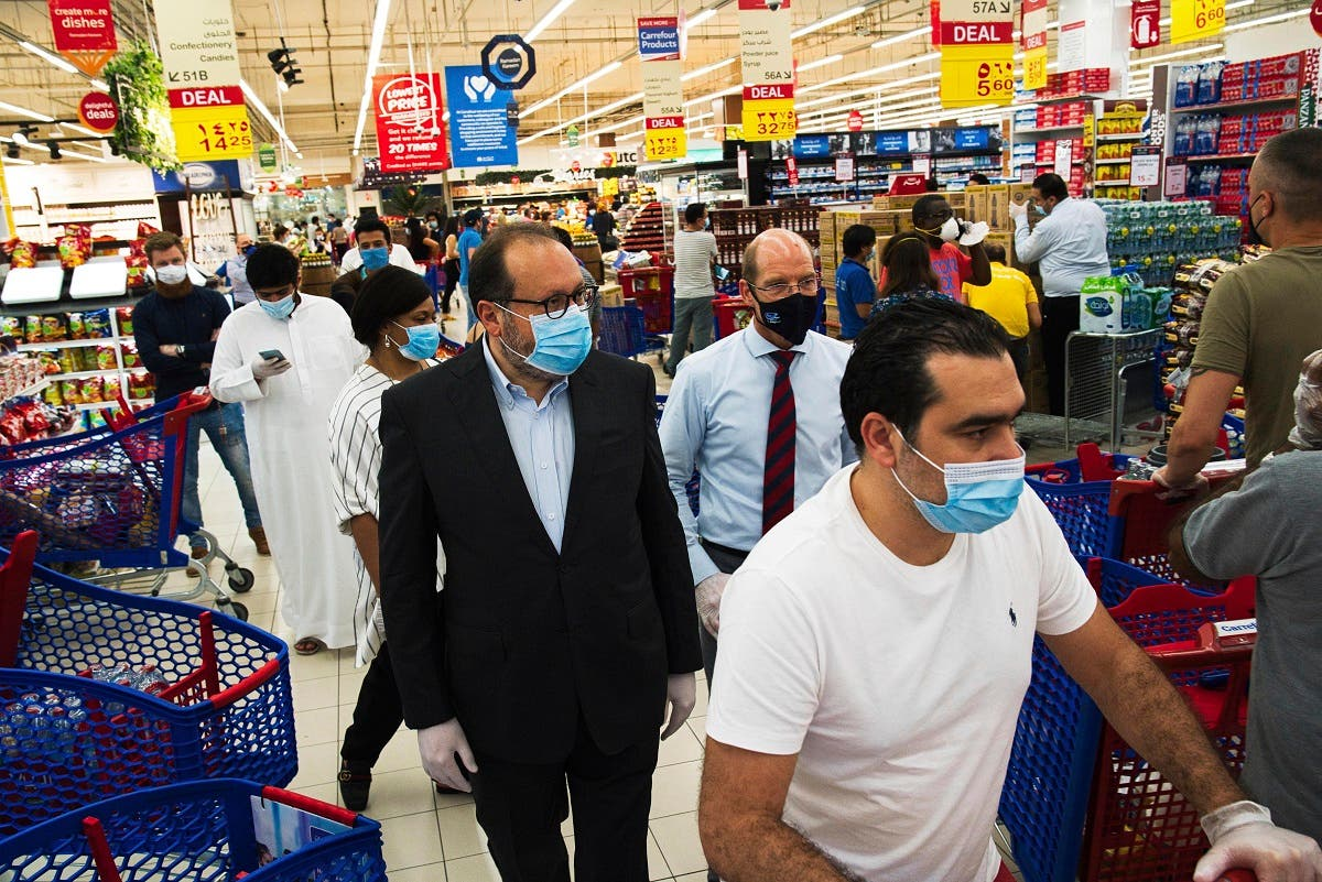 In this Sunday, April 19, 2020 photo, Majid Al Futtaim CEO Alain Bejjani, (center left), and store manager Arnaud Bouf (center), walk through heavy shopping traffic during the coronavirus pandemic in the world's busiest Carrefour supermarket, at the Mall of the Emirates in Dubai, UAE. (AP)