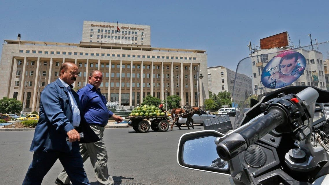 Men walk outside the Central Bank of Syria headquarters in the Sabaa Bahrat Square of the capital Damascus. (AFP)