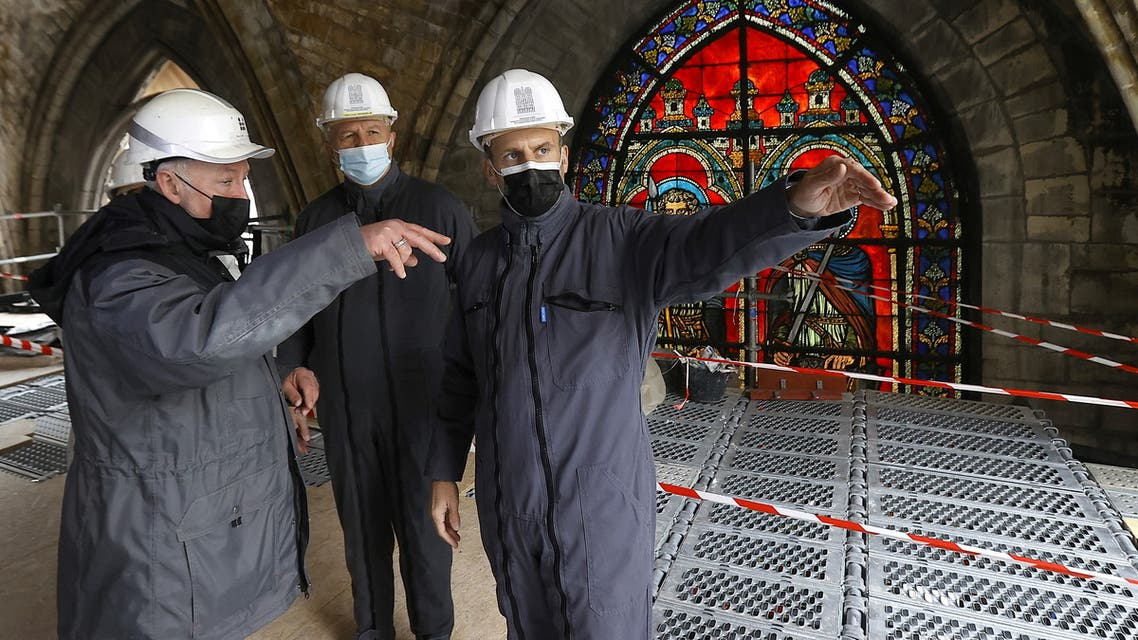 French President Emmanuel Macron speaks with a worker and the French Army General Jean-Louis Georgelin in front of a stained glass window under the damaged vaults during a visit at the reconstruction site of the Notre-Dame de Paris Cathedral, which was damaged in a devastating fire two years ago, as restoration works continue, in Paris, France, April 15, 2021. (Reuters)