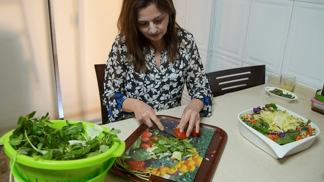 Hala Sheikh prepares Fattoush, a popular salad, at her house in Beirut, Lebanon April 13, 2021. (Reuters)