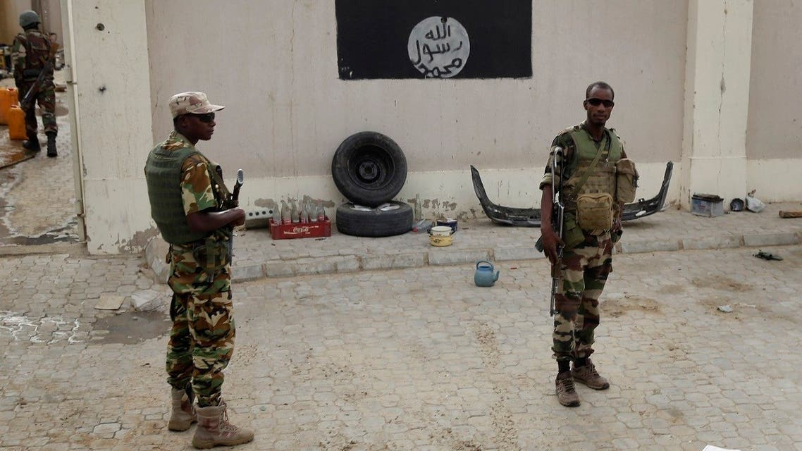 Chadian soldiers stand at a checkpoint in front of a Boko Haram flag the Nigerian city of Damasak, Nigeria. (AP)