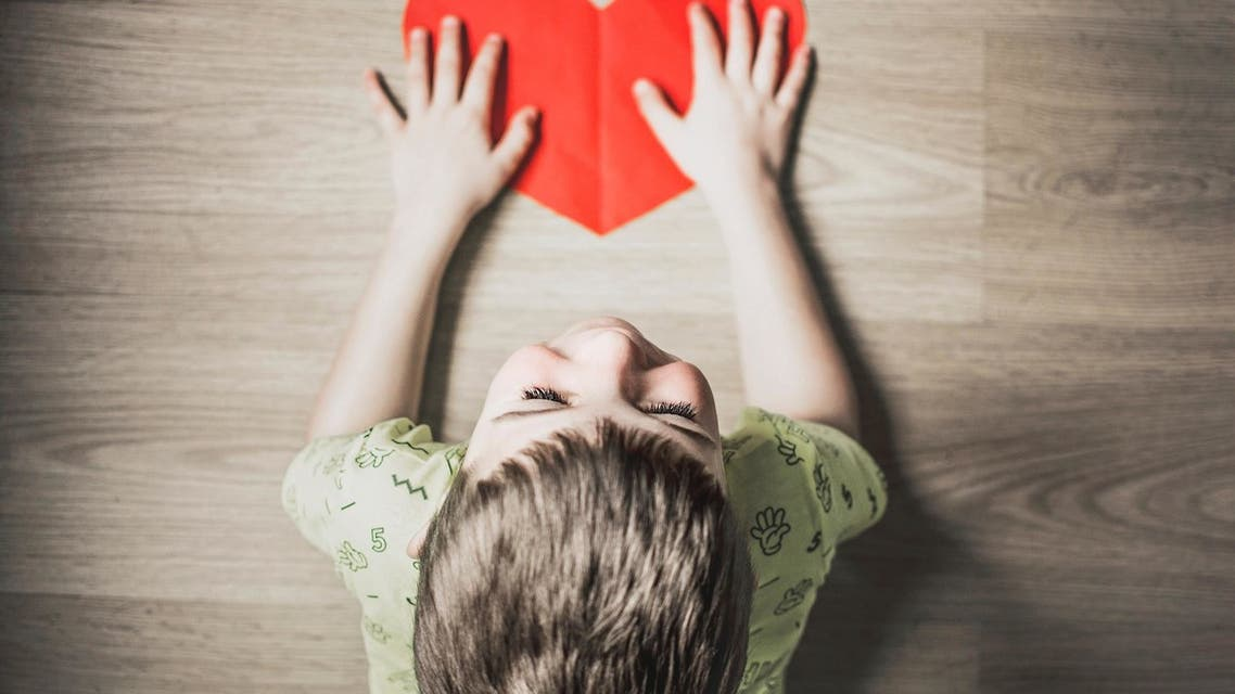 A child holding a heart cut out of paper. (Unsplash)