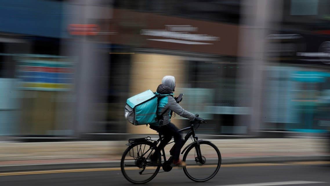 A deliveroo delivery driver cycles through the centre of Manchester, Britain, on March 8, 2021. (Reuters)