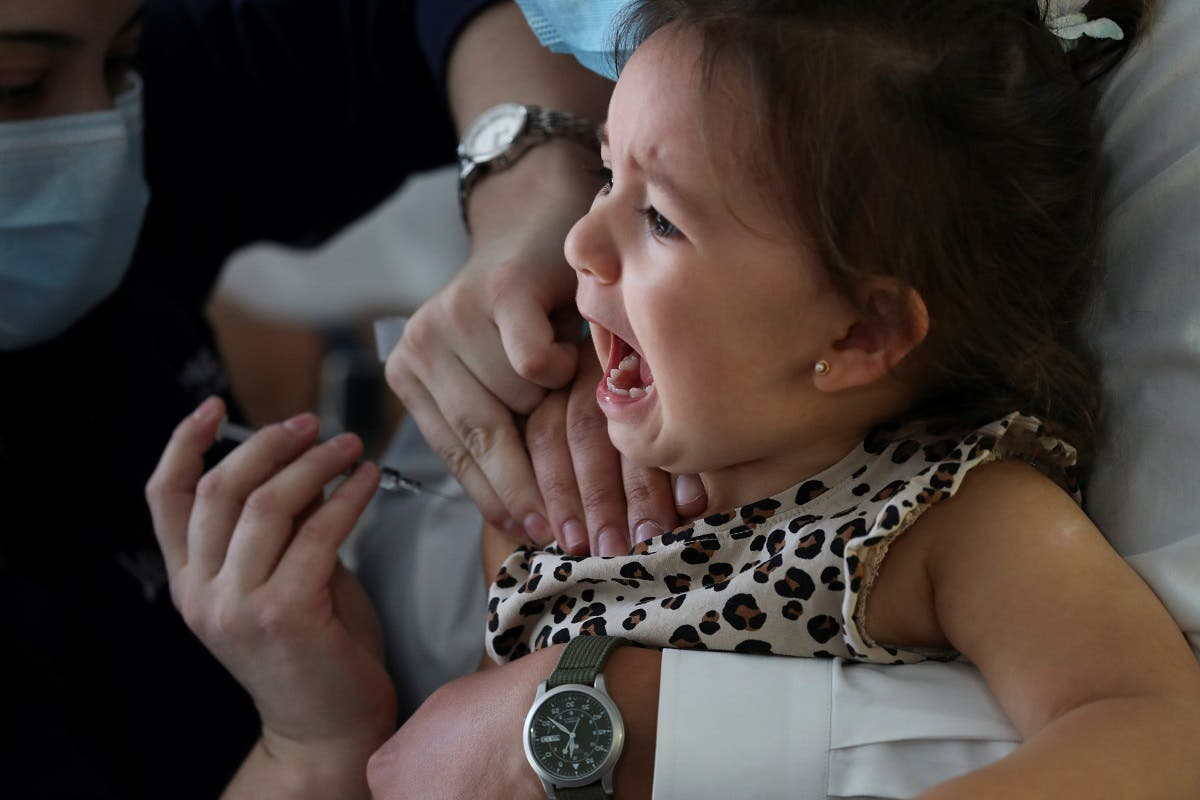 A child reacts while receiving a vaccine as part of the seasonal flu vaccination campaign for children and elderly people, during the coronavirus pandemic, in Santiago, Chile, on April 13, 2021. (Reuters)