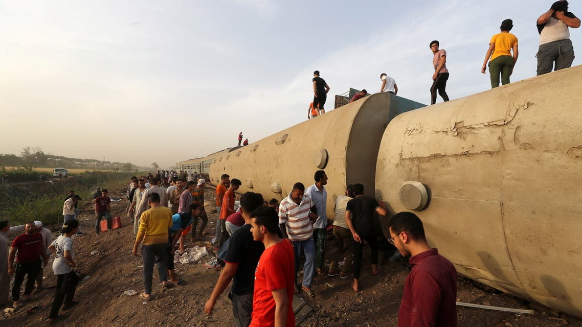 People gather at the site where train carriages derailed in Qalioubia province, north of Cairo, Egypt April 18, 2021. REUTERS/Mohamed Abd El Ghany TPX IMAGES OF THE DAY