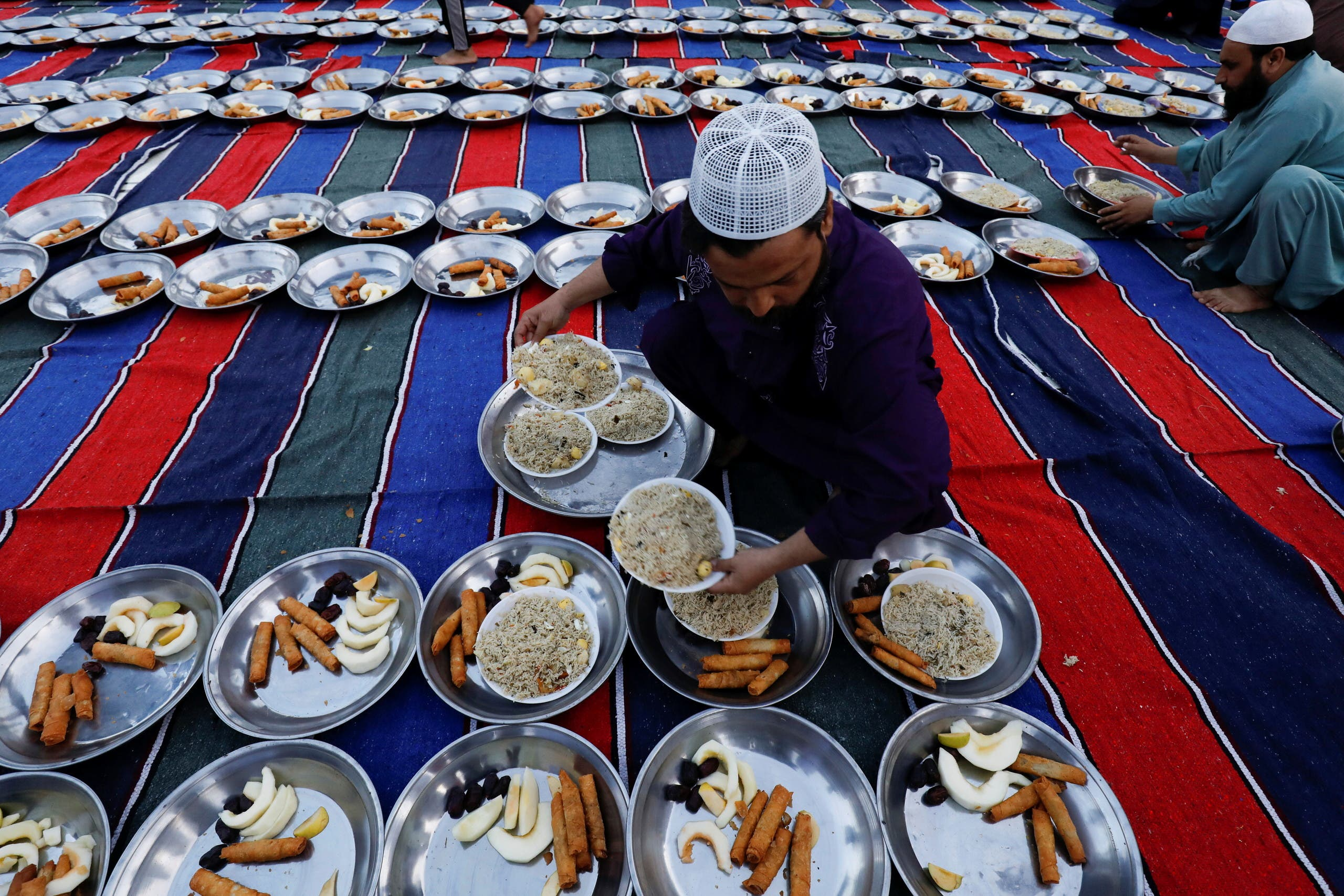 A man arranges plates of food for Iftar (breaking fast) meal during the fasting month of Ramadan, as the outbreak of the coronavirus disease (COVID-19) continues, at a mosque in Karachi, Pakistan. (Reuters)