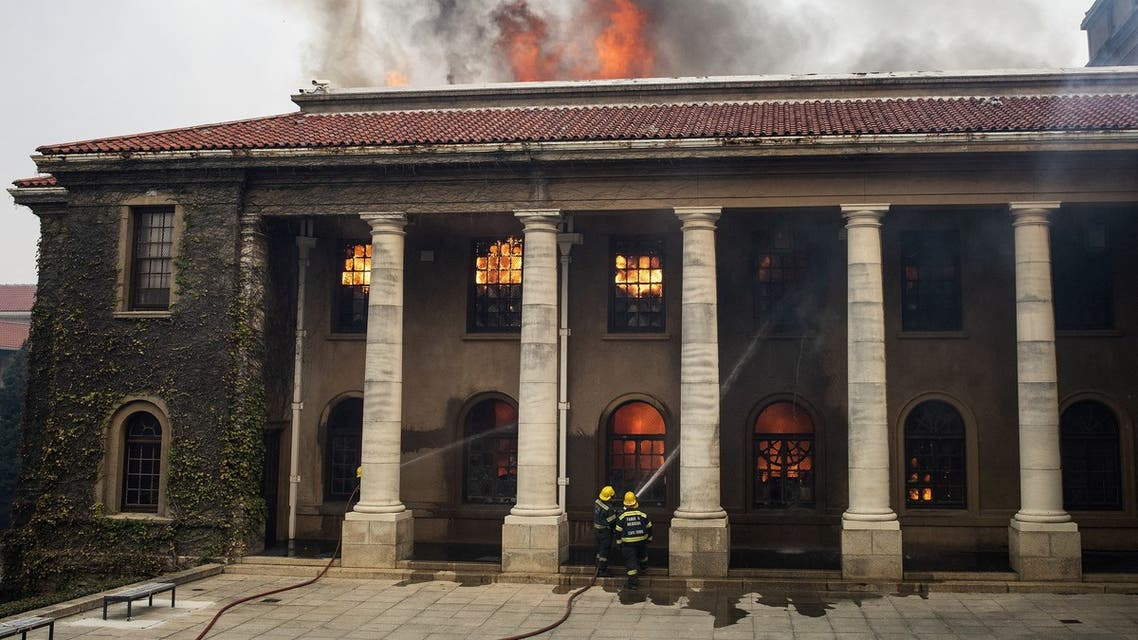 Firefighters try, in vain, to extinguish a fire in the Jagger Library, at the University of Cape Town, after a forest fire came down the foothills of Table Mountain, setting university buildings alight in Cape Town, on April 18, 2021. (AFP)