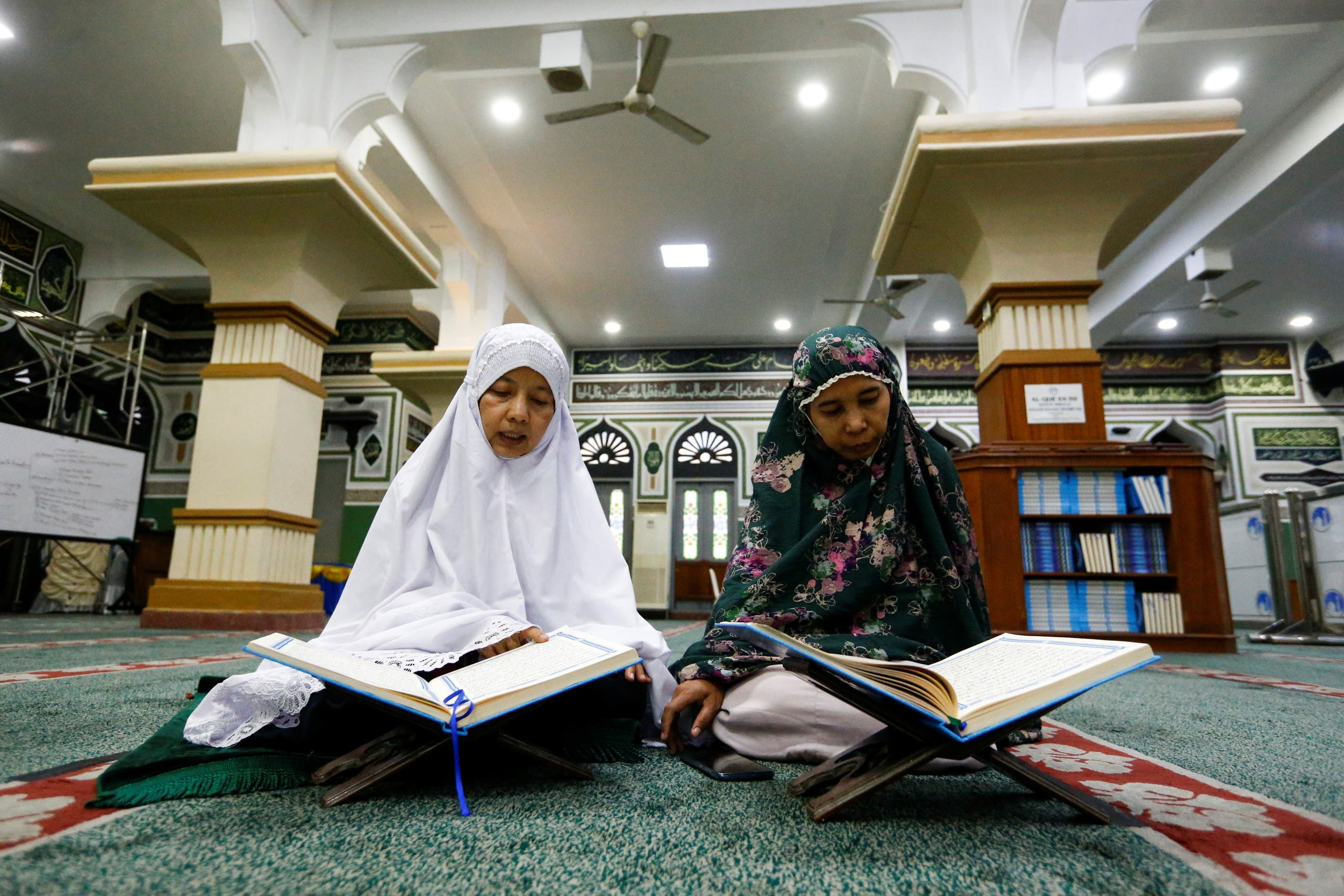 Women read the Quran as they wait to break the fast during the holy month of Ramadan, amid the coronavirus disease (COVID-19) pandemic, in Jakarta, Indonesia. (Reuters)