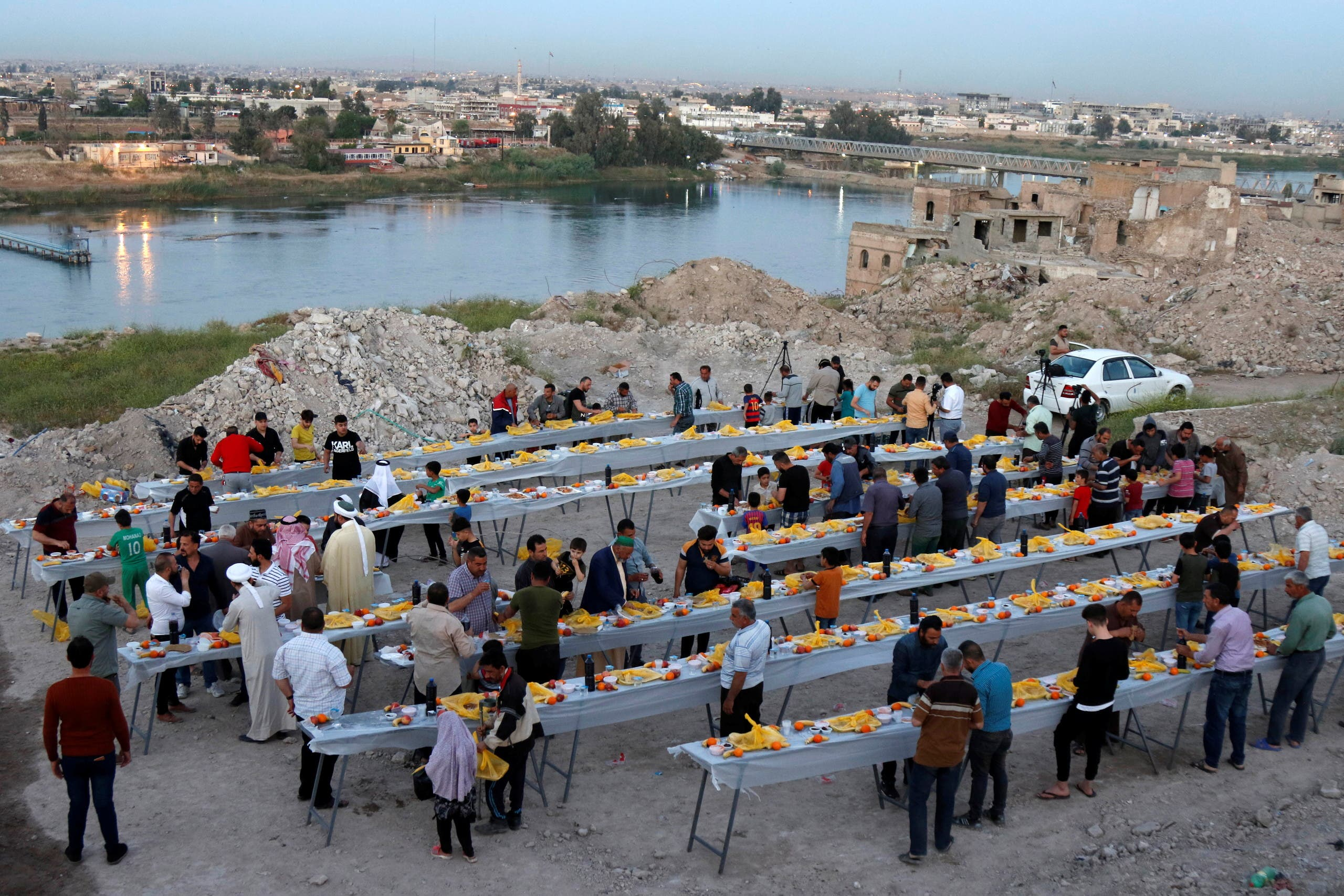 People gather to have their Iftar (breaking fast) meals during the fasting month of Ramadan, in Mosul, Iraq. (Reuters)