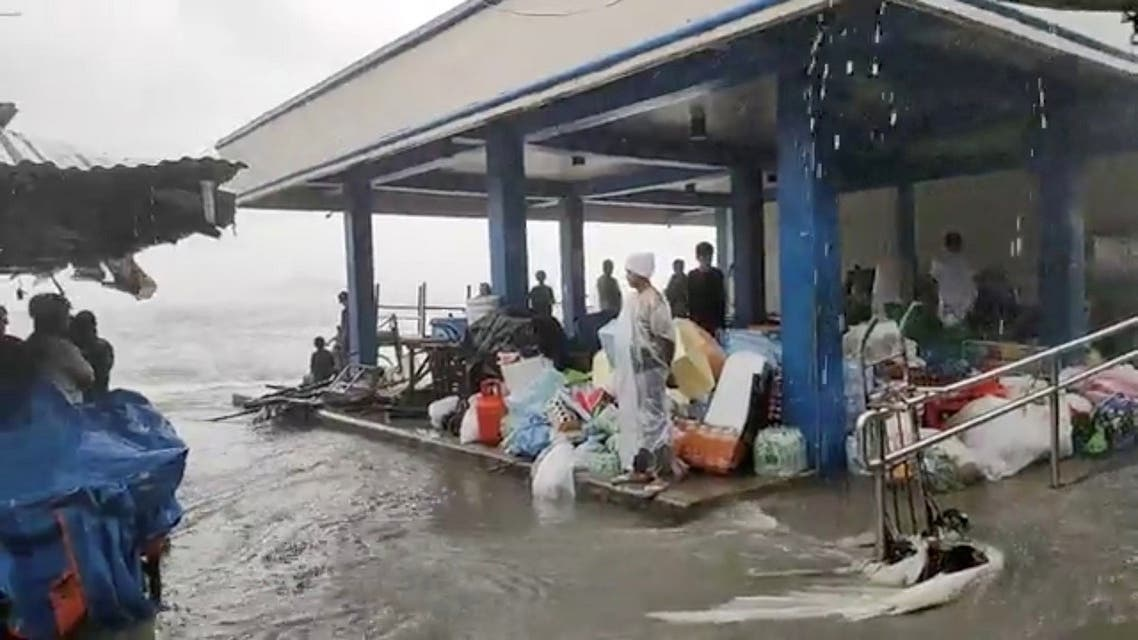 People stand in cover on a flooded market as Super Typhoon Surigae moves close to the Philippines in the province of Catbalogan, Samar, Philippines , onApril 18, 2021, in this screen grab obtained from a social media video. (Reuters)