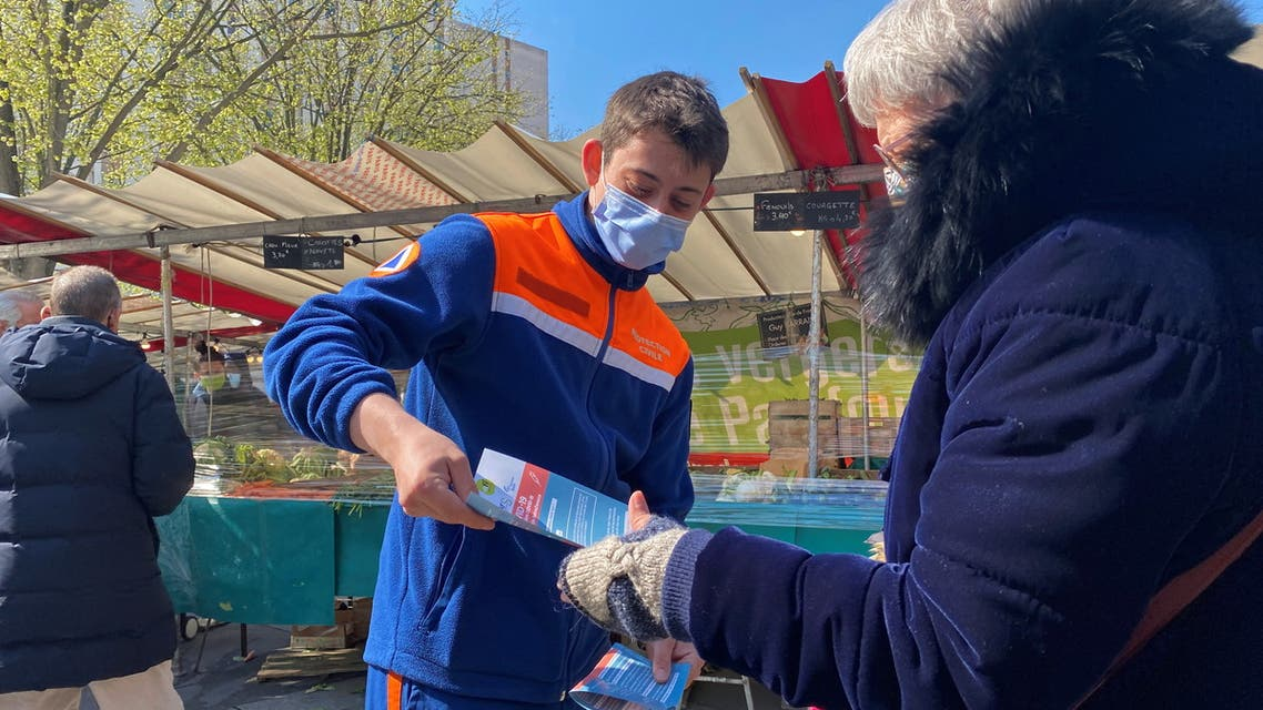 Volunteers from French Protection Civile association hand out leaflets at a fresh producer market to try to persuade Parisians over 55 to take AstraZeneca vaccine, amid the coronavirus disease (COVID-19) pandemic, in Paris, France, April 16, 2021. Picture taken April 16, 2021. (Reuters)