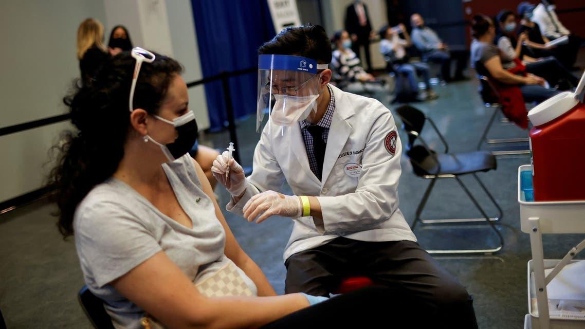 FILE PHOTO: A woman receives a dose of the Johnson & Johnson coronavirus disease (COVID-19) vaccine at vaccination center in Chinatown, in Chicago, Illinois, U.S., April 6, 2021. REUTERS/Carlos Barria/File Photo