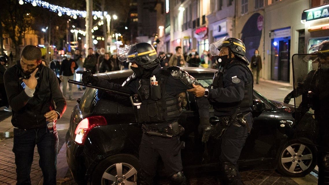 A French riot policeman is restrained as he gestures at a protester, Nov. 28, 2020 in Marseille, France. (Reuters)
