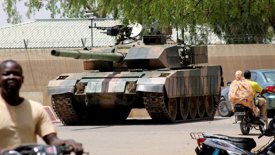 People drive past a Chad army tank near presidential palace, in N'djamena, Chad, on April 19, 2021. (Reuters)