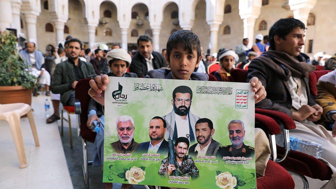 A boy holds a poster of Houthi slain commanders in Sanaa, Yemen, Jan. 2, 2021. (Reuters)