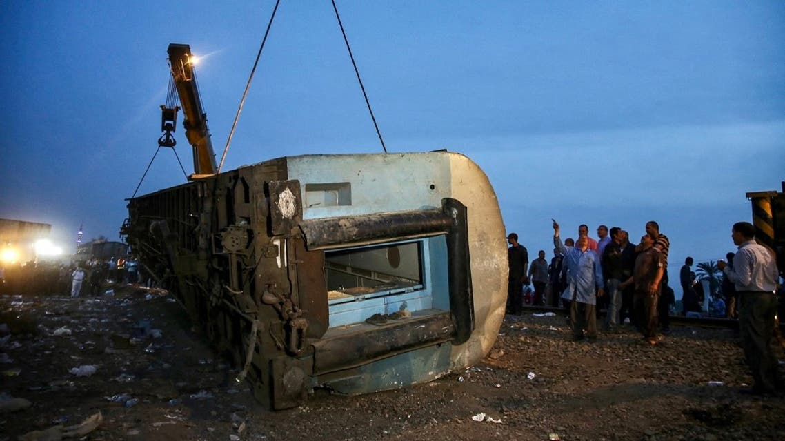 People stand by as a telescopic railway crane lifts an overturned passenger carriage, at the scene of a railway accident in the city of Toukh in Egypt's central Nile Delta province of Qalyubiya on April 18, 2021. (Ayman Aref/AFP)