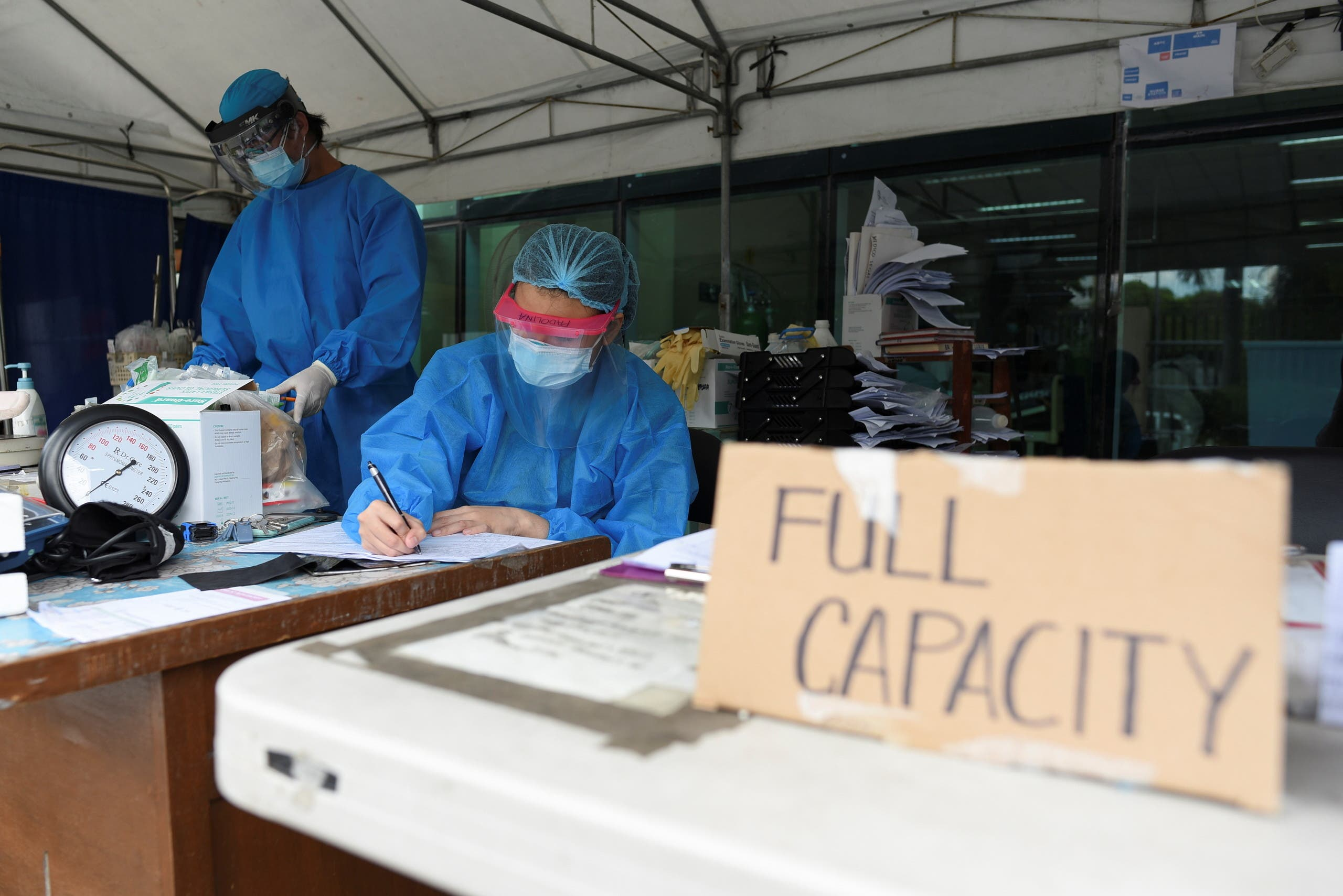 Health workers sort patients' files at a triage area in Santa Ana Hospital, where a sign indicating that the hospital's coronavirus disease (COVID-19) facility is at full capacity is displayed, in Manila, Philippines. (Reuters)