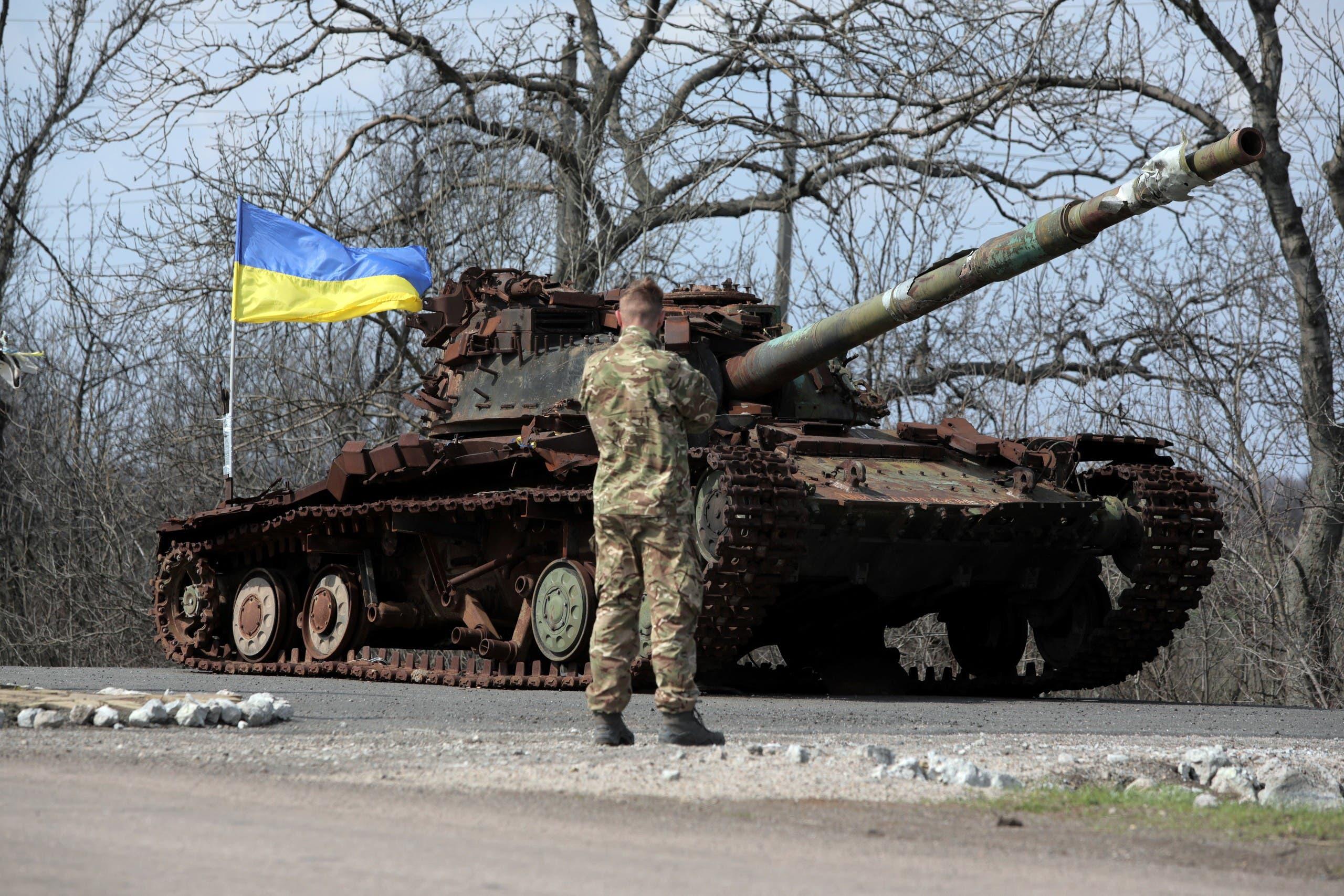 جندي أوكراني يقف بجوار دبابة أوكرانية دمرت عام 2014 من قبل الانفصاليين المدعومين من روسيا في منطقة دونيتسك يوم 21 أبريل
