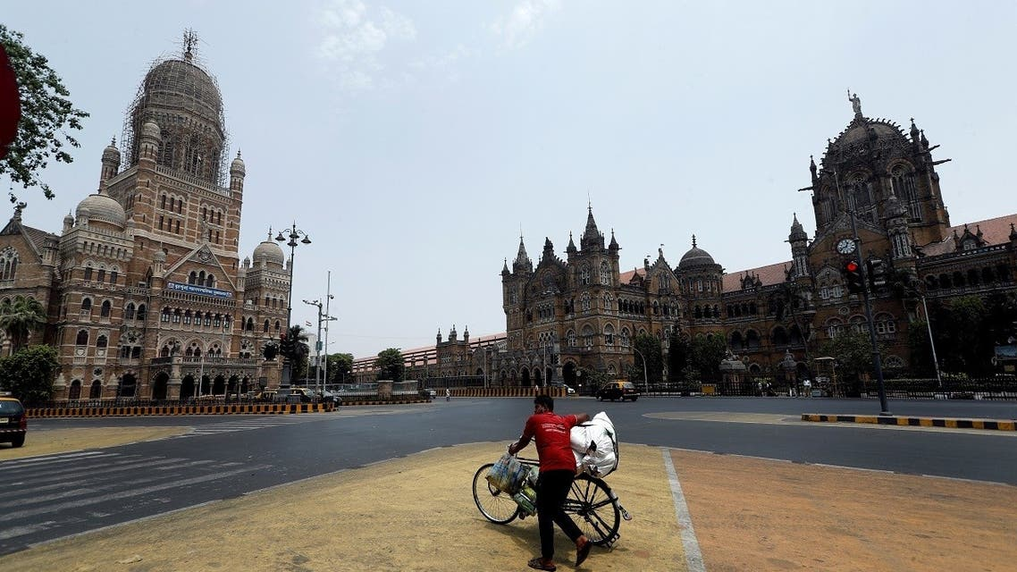 A man walks with his bicycle in front of the Brihanmumbai Municipal Corporation (BMC) building and the Chhatrapati Shivaji Maharaj Terminus (CSMT) during a weekend lockdown to limit the spread of the coronavirus disease (COVID-19) in Mumbai, India. (Reuters)