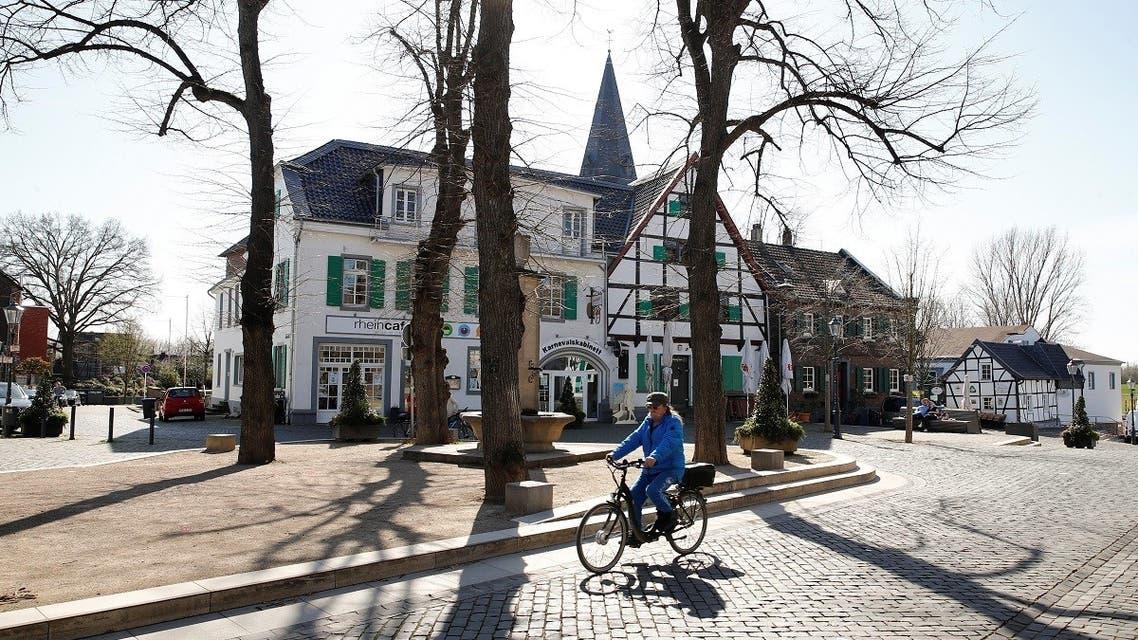 A man cycles through the North-Rhine Westphalian town of Monheim am Rhein, Germany, March 30, 2021. (Reuters)