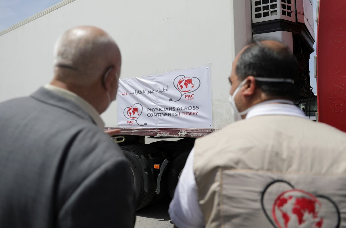 Healthcare workers stand near a truck carrying vaccines against the coronavirus disease (COVID-19) at Bab al-Hawa crossing at the Syrian-Turkish border, in Idlib governorate, Syria, on April 21, 2021. (Reuters)