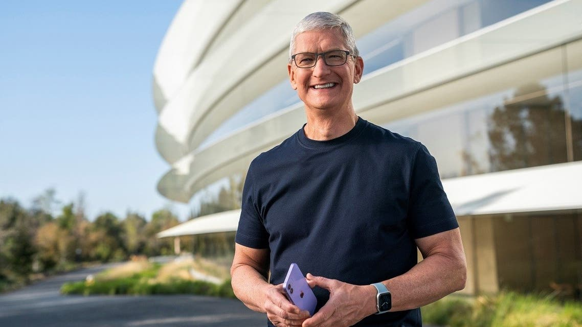 Apple CEO Tim Cook holds an iPhone 12 in a new purple finish, in this still image from the keynote video of a special event at Apple Park in Cupertino, California, US, on April 20, 2021. (Reuters)