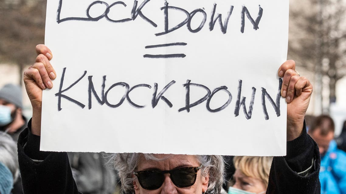 A demonstrator displays a placard reading Lockdown = knockdown during a demonstration by anti lockdown critics and so-called 'Querdenker' in Berlin on April, 13, 2021, amid the Covid-19, corona pandemic.  (File photo: AFP)