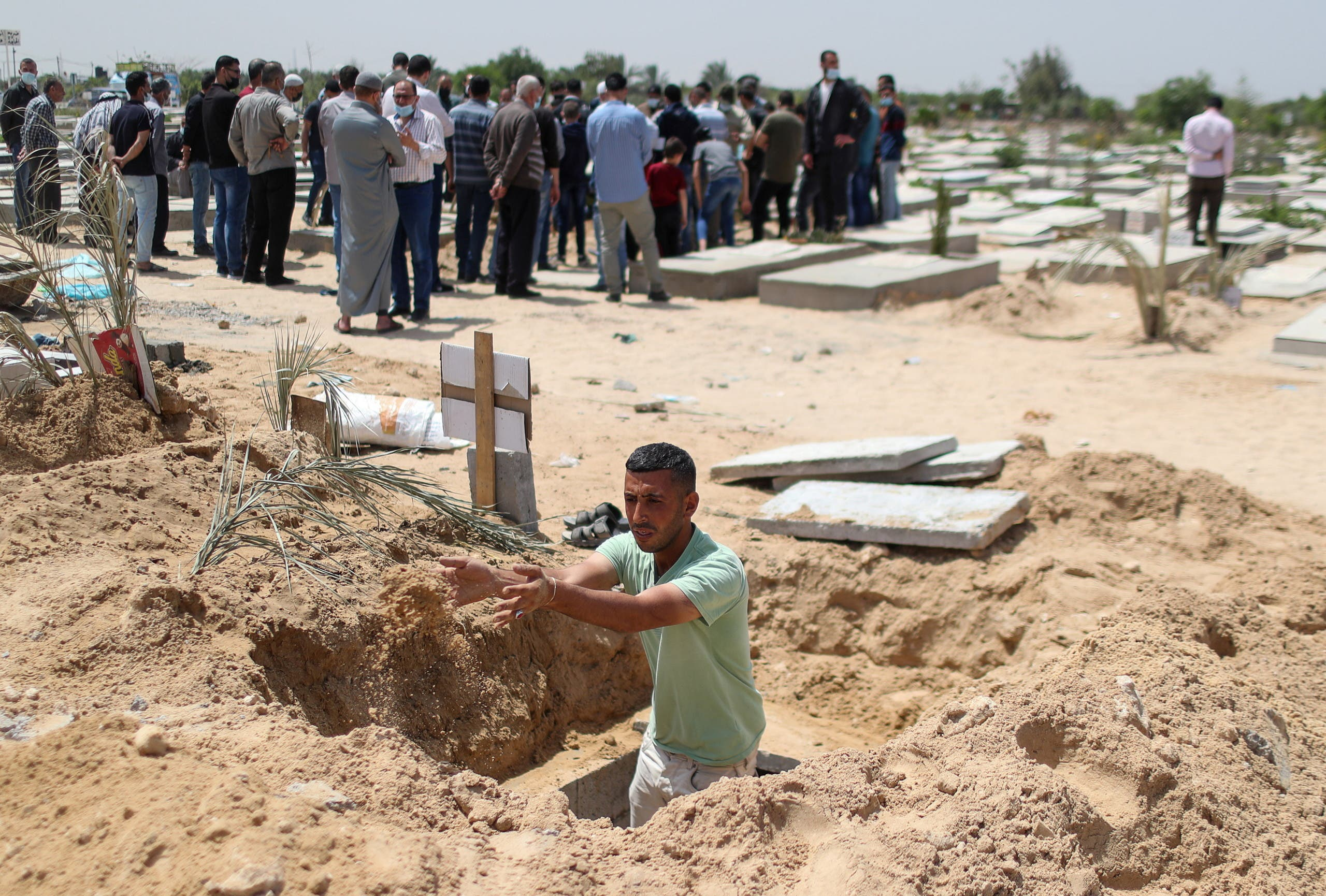 Palestinian worker Mohammad al-Haresh, 30, digs a grave for a coronavirus disease (COVID-19) victim, at a cemetery, east of Gaza City April 20, 2021. Picture taken April 20, 2021. (Reuters)