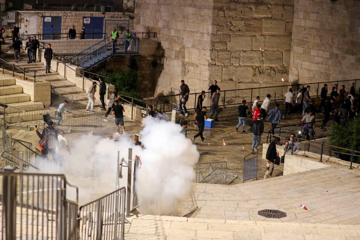Palestinians run away as a stun grenade fired by Israeli police explodes during clashes at Damascus Gate just outside Jerusalem's Old City, on the Muslim holy fasting month of Ramadan on April 17, 2021. (Reuters)