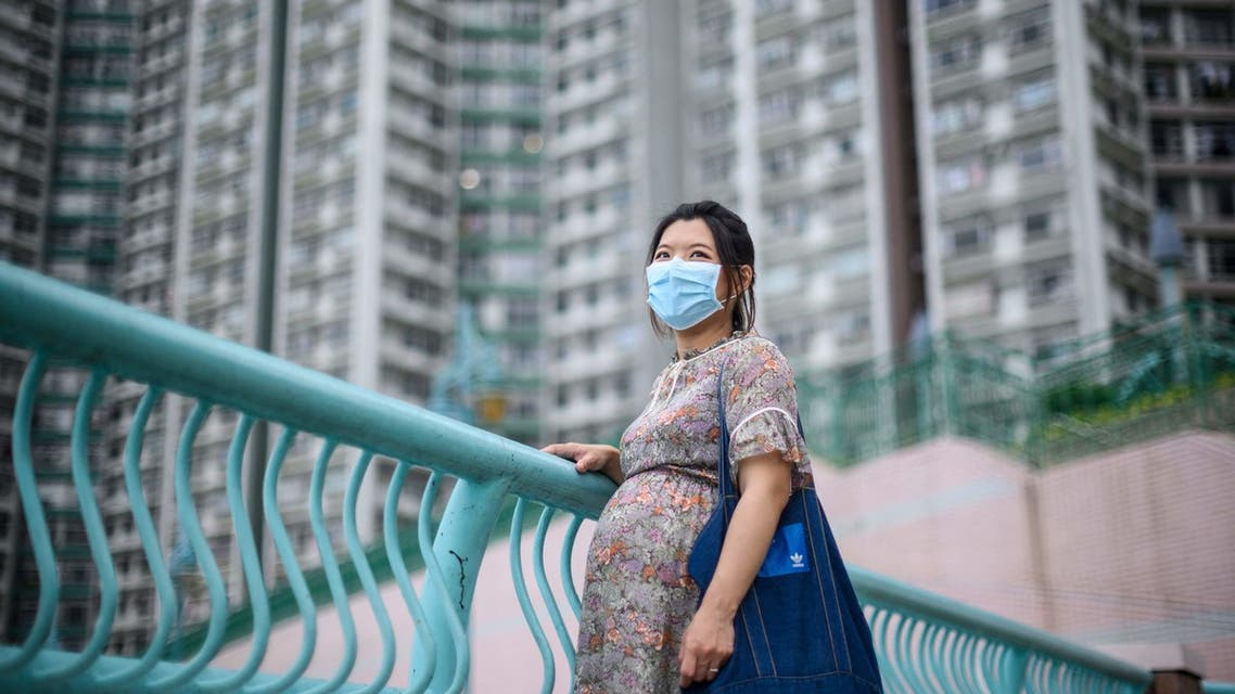 In this picture taken on March 31, 2020, expectant mother Jamie Chui, 33, poses in front of residential buildings near where she lives in Hong Kong. Jamie Chui has been a virtual prisoner in her Hong Kong home for most of her nine-month pregnancy. Trapped intially by violent pro-democracy protests and tear gas, and then by the coronavirus -- she now faces giving birth alone, with her husband unlikely to see his child until days later.