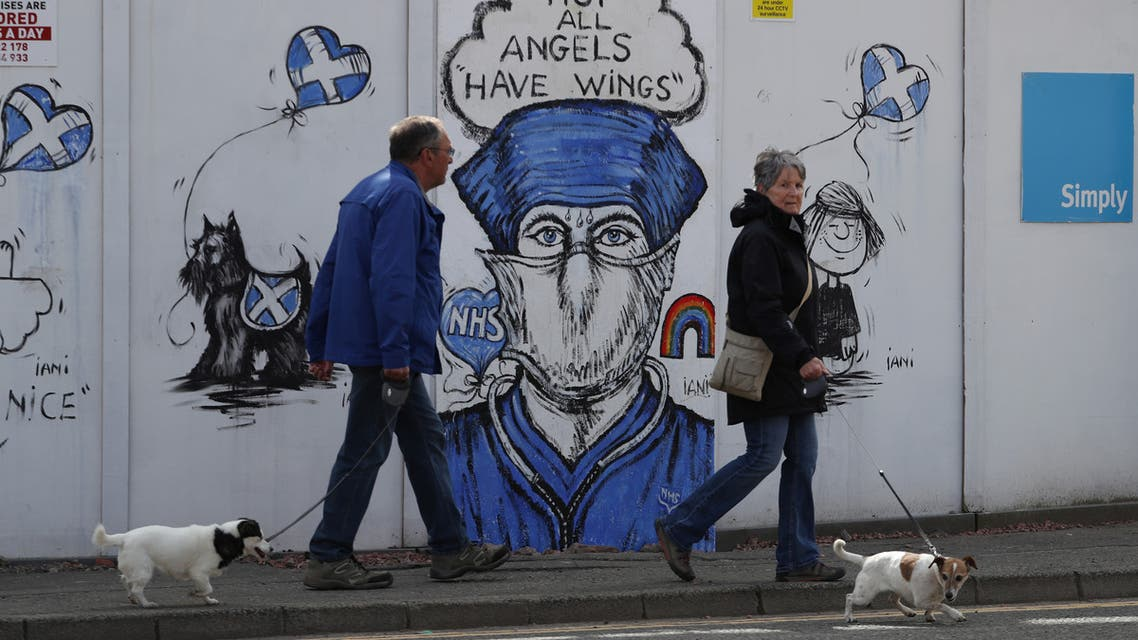 People are seen walking their dogs while passing a graffiti in support of the NHS, as the spread of the coronavirus disease (COVID-19) continues, Perth, Scotland, Britain, April 27, 2020. (File photo: Reuters)