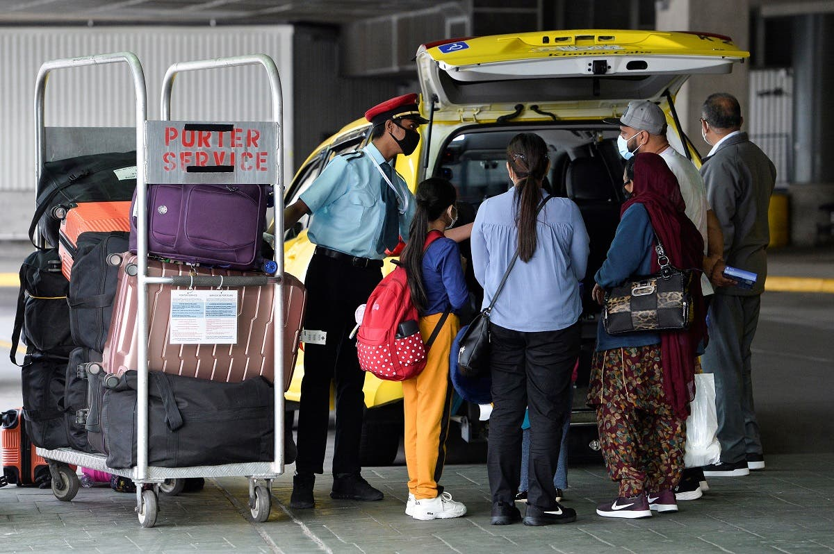 A porter loads the luggage of recently arrived air travelers from New Delhi, into a cab after Canada's government temporarily barred passenger flights from India and Pakistan for 30 days, at Vancouver International Airport in Richmond. (Reuters)