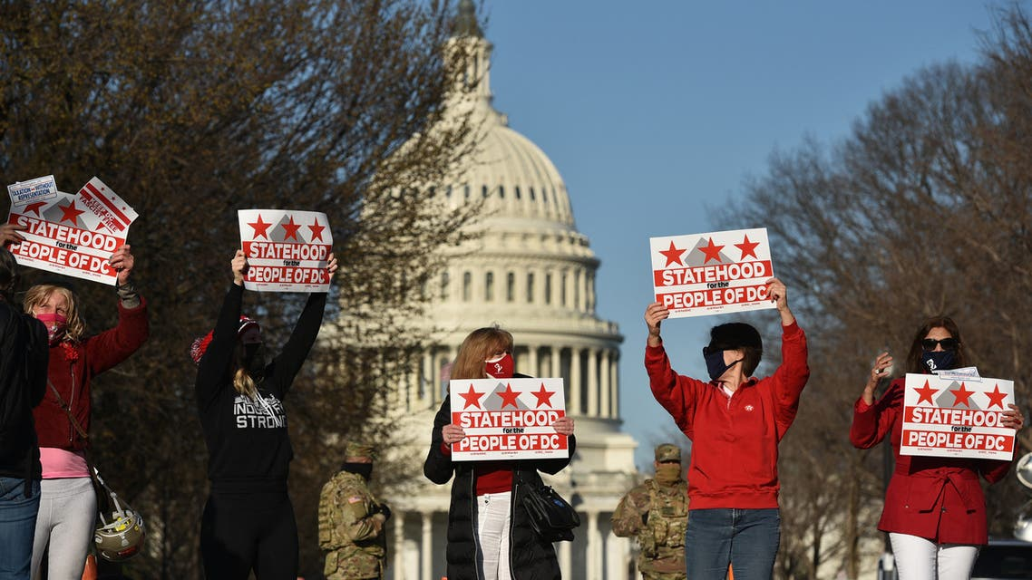 Activists hold signs as they take part in a rally in support of DC statehood near the US Capitol in Washington, DC on March 22, 2021. Democrats emboldened by their control of the US House, Senate and White House launched a fresh push Monday for statehood for the nation's capital Washington, beginning with a high-profile congressional hearing addressing the issue.