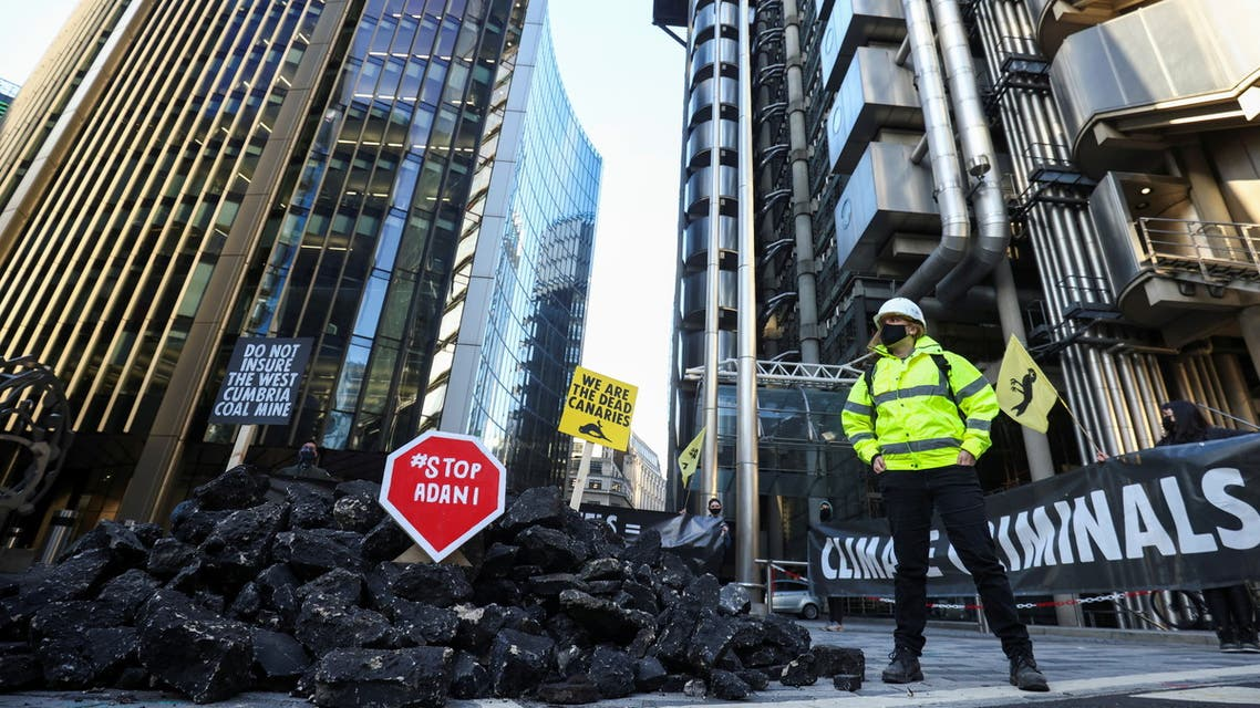 Activists from Extinction Rebellion, a global environmental movement, stand next to fake coal, made from rocks, during a protest outside the Lloyd's building in London, Britain April 23, 2021. (Reuters)