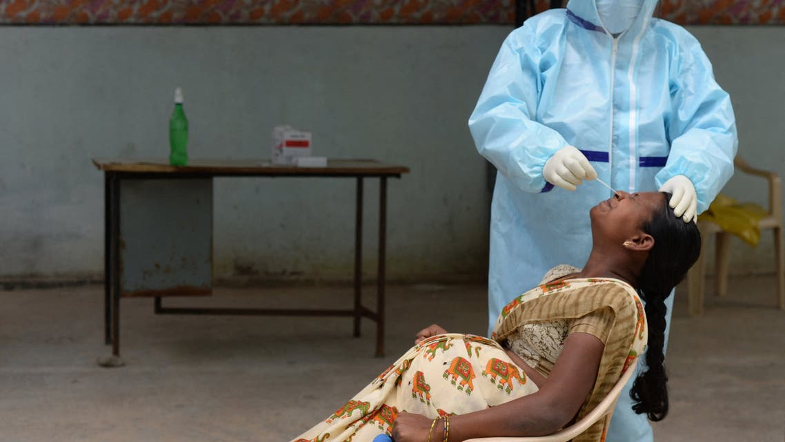 A health worker wearing Personal Protective Equipment (PPE) gear collects a swab sample of a pregnant woman at a free COVID-19 coronavirus testing centre at Medchal Malkajgiri district on the outskirts of Hyderabad on August 24, 2020. India's confirmed coronavirus cases crossed the three million mark on August 23 with nearly 70,000 new infections, as the disease continues to surge in the world's second most-populous nation.