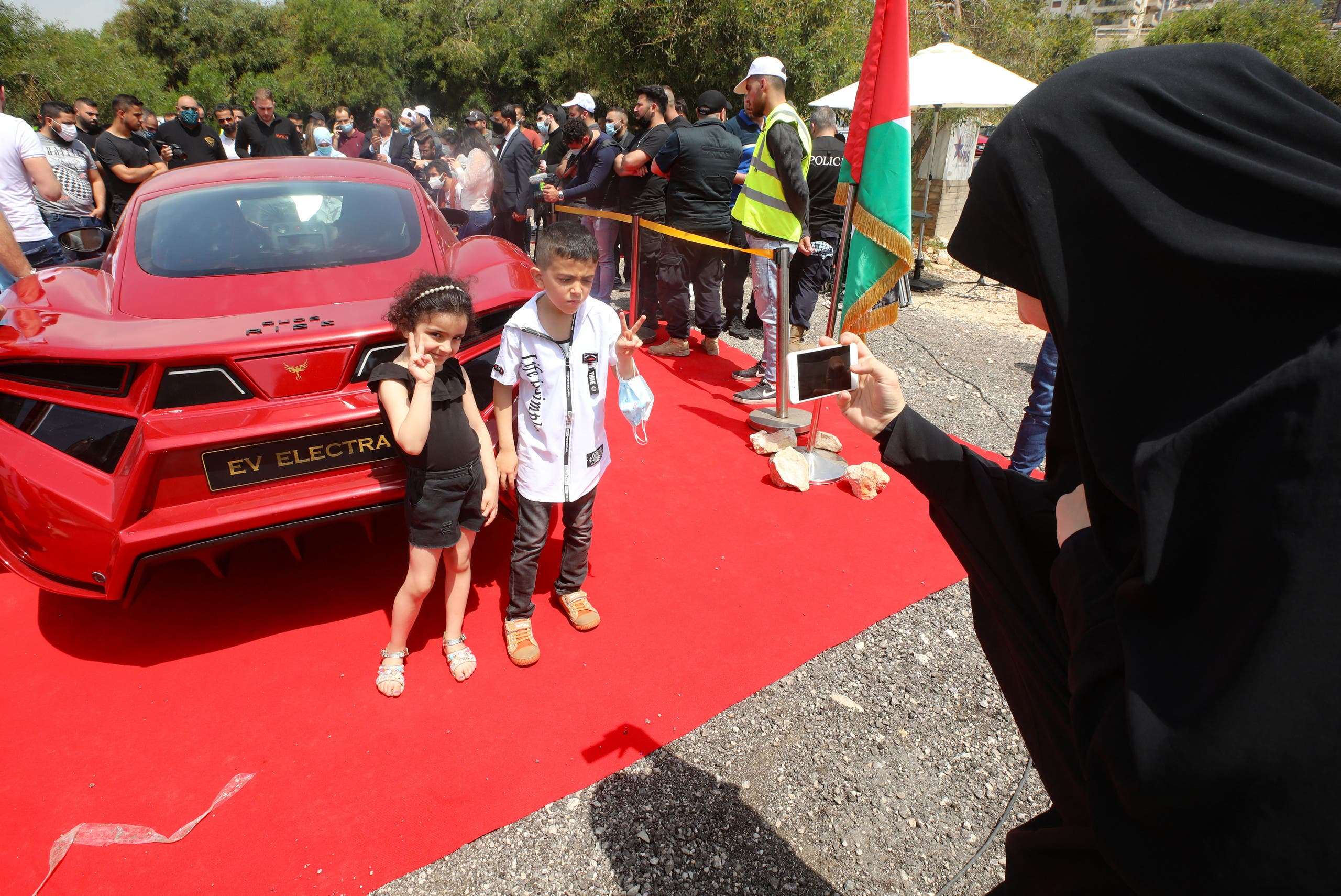 A woman takes pictures of children posing by the Quds Rise, the first ever electric car produced in Lebanon, during an unveiling ceremony in Khaldeh, south of the capital Beirut, on April 24, 2021. (AFP)