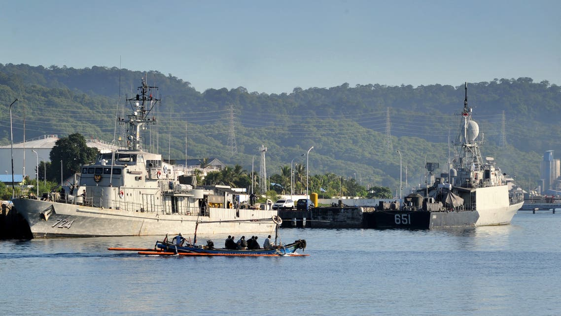 An outrigger canoe sails past Indonesian Navy ships at the naval base in Banyuwangi, East Java province, on April 24, 2021, as the military continues search operations off the coast of Bali for the Navy's KRI Nanggala submarine that went missing April 21 during a training exercise. (AFP)
